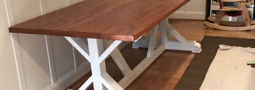 Completed trestle style dining table with pecan stain and painted white base.
