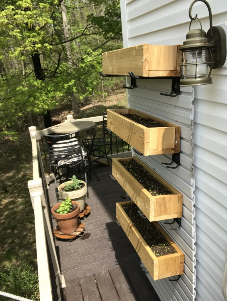Cedar planters mounted vertically to the side of the house