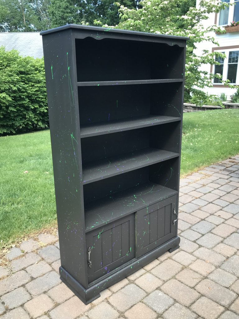 Black painted bookcase with whimsical paint splatter
